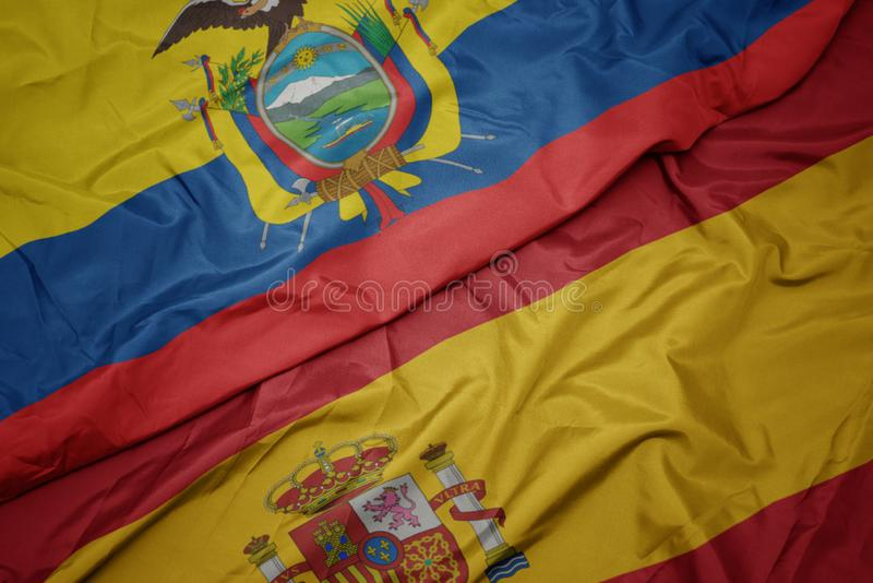 Waving colorful flag of spain and national flag of ecuador. Macro stock photo