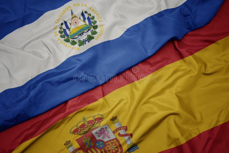 Waving colorful flag of spain and national flag of el salvador. Macro stock photography