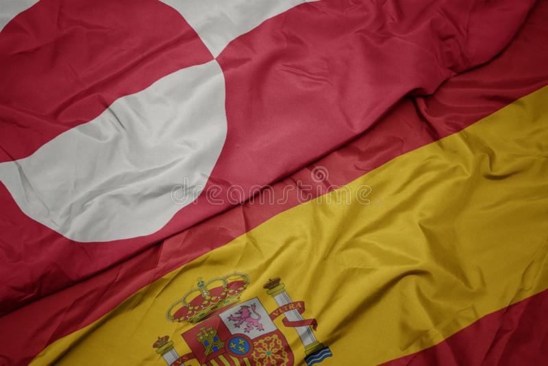 Waving colorful flag of spain and national flag of greenland. Macro stock image