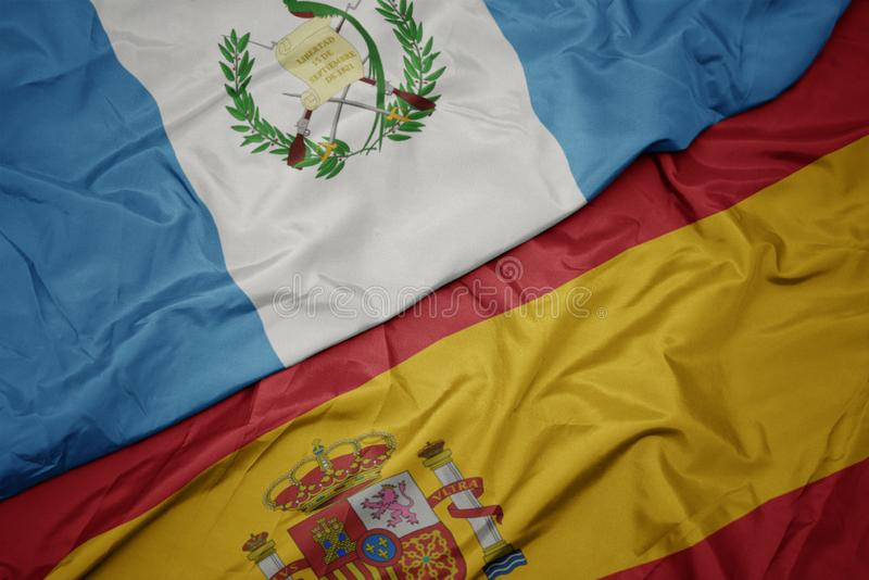 Waving colorful flag of spain and national flag of guatemala. Macro royalty free stock image