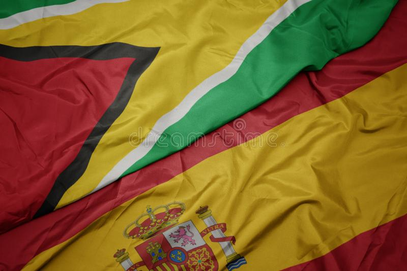 Waving colorful flag of spain and national flag of guyana. Macro royalty free stock photos