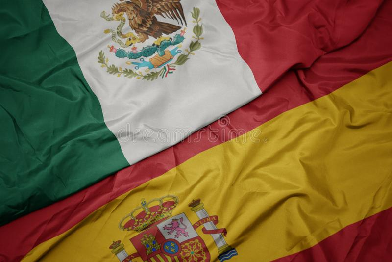 Waving colorful flag of spain and national flag of mexico. Macro royalty free stock photos