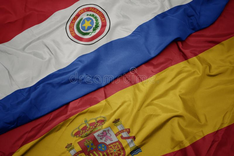 Waving colorful flag of spain and national flag of paraguay. Macro royalty free stock image