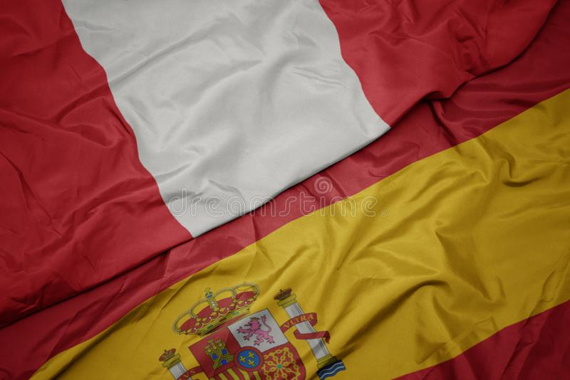 Waving colorful flag of spain and national flag of peru. Macro stock image