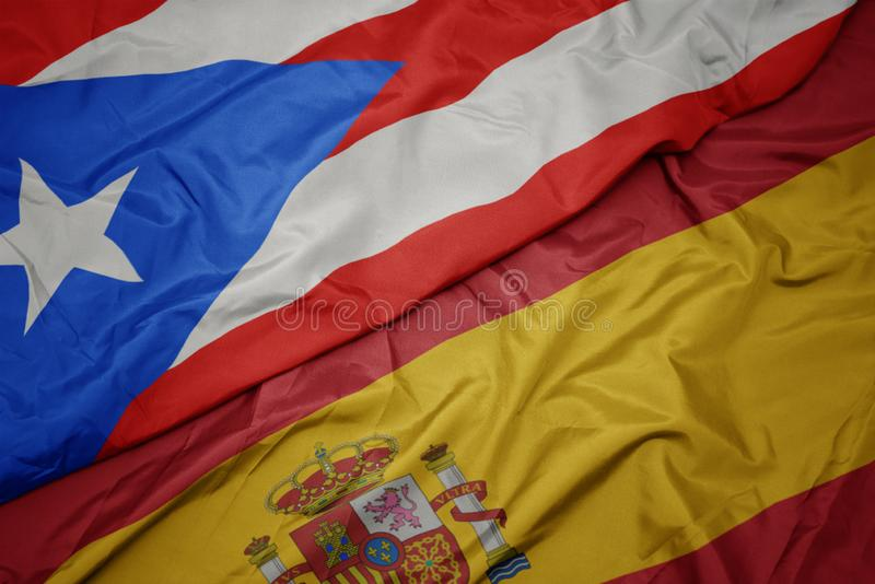 Waving colorful flag of spain and national flag of puerto rico. Macro royalty free stock images