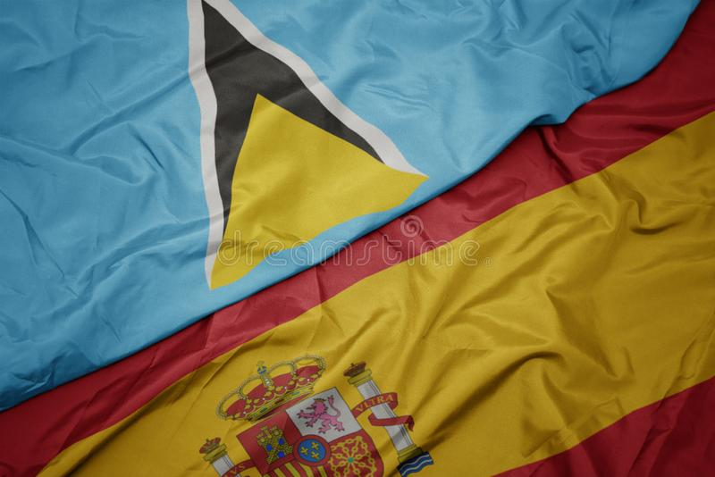 Waving colorful flag of spain and national flag of saint lucia. Macro royalty free stock images