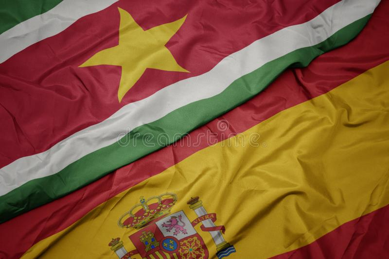 Waving colorful flag of spain and national flag of suriname. Macro royalty free stock images