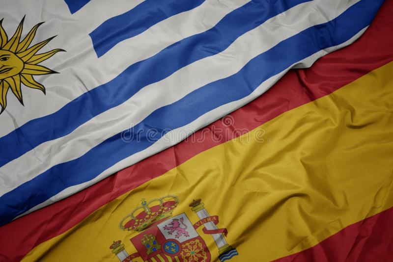 Waving colorful flag of spain and national flag of uruguay. Macro royalty free stock images