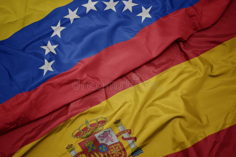 Waving colorful flag of spain and national flag of venezuela. Macro stock photo