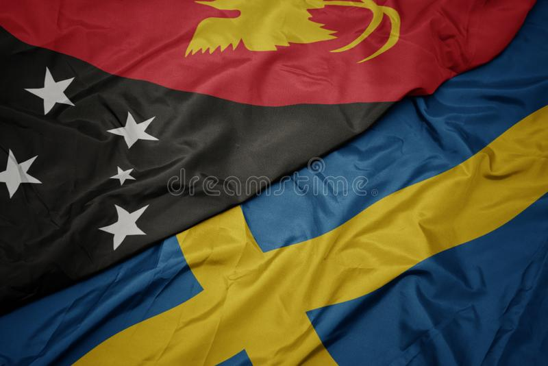 Waving colorful flag of sweden and national flag of Papua New Guinea. Macro royalty free illustration