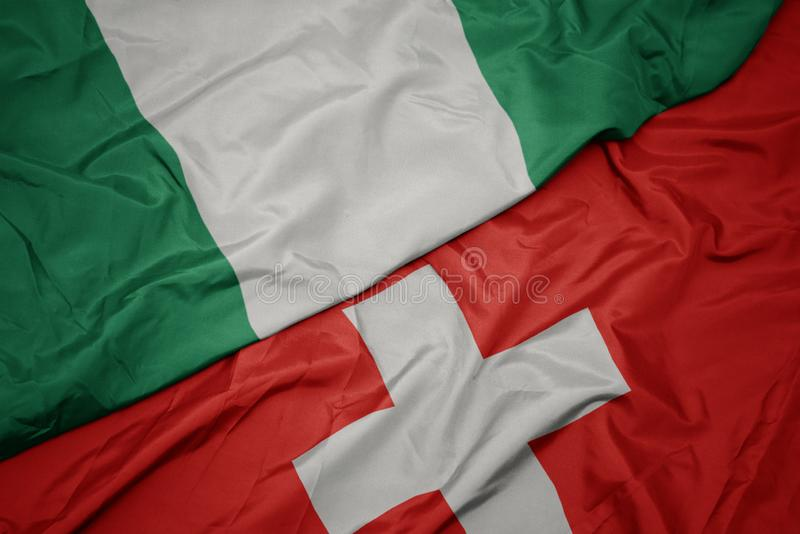 Waving colorful flag of switzerland and national flag of nigeria. Macro royalty free stock image