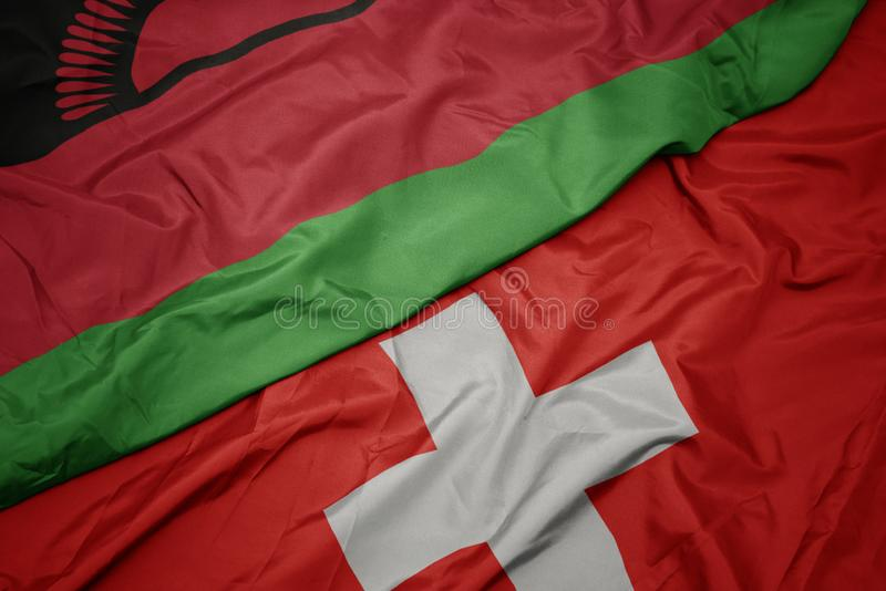 Waving colorful flag of switzerland and national flag of malawi. Macro royalty free stock photography