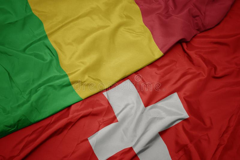 Waving colorful flag of switzerland and national flag of mali. Macro stock images