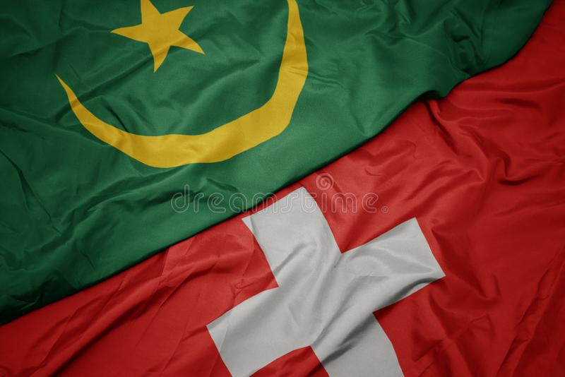 Waving colorful flag of switzerland and national flag of mauritania. Macro royalty free stock photo