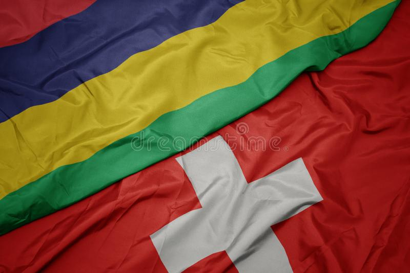 Waving colorful flag of switzerland and national flag of mauritius. Macro royalty free stock photography