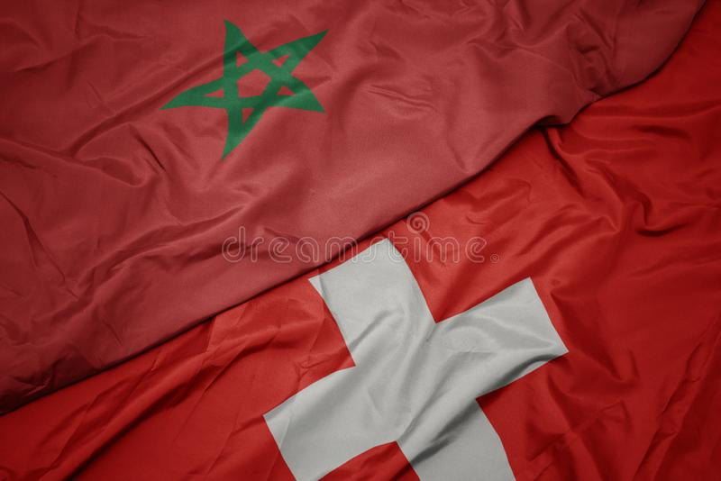 Waving colorful flag of switzerland and national flag of morocco. Macro stock photo