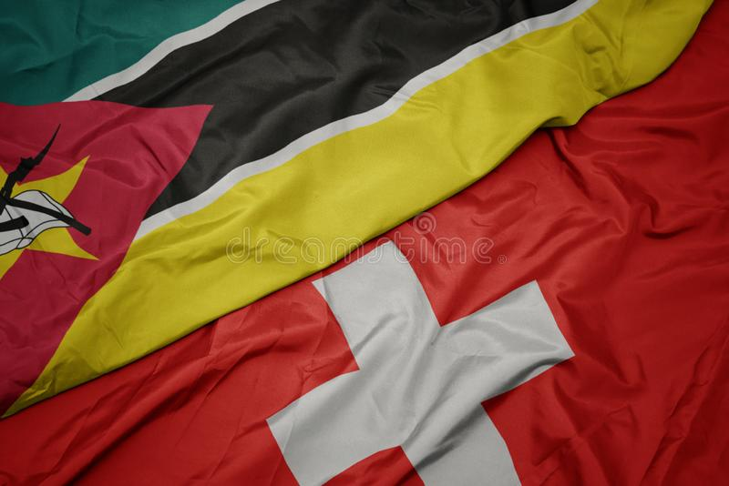 Waving colorful flag of switzerland and national flag of mozambique. Macro stock photos