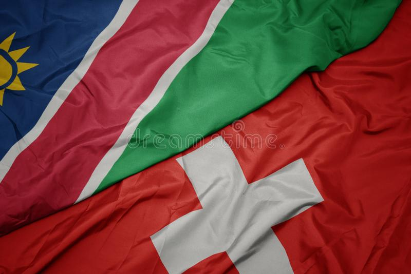 Waving colorful flag of switzerland and national flag of namibia. Macro stock photography