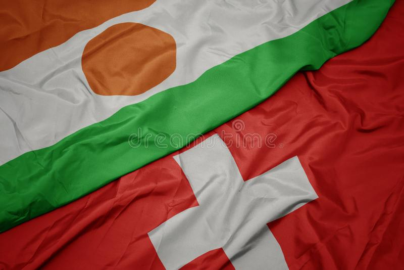 Waving colorful flag of switzerland and national flag of niger. Macro stock photography