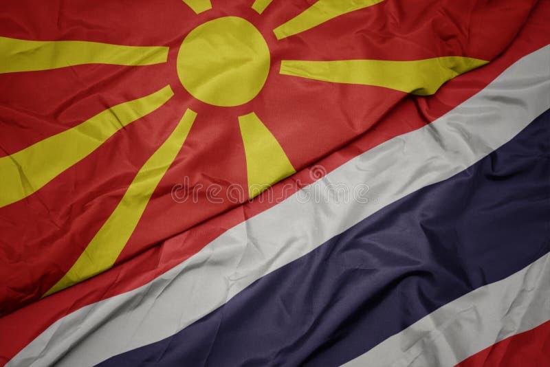 Waving colorful flag of thailand and national flag of macedonia. Macro royalty free stock photography