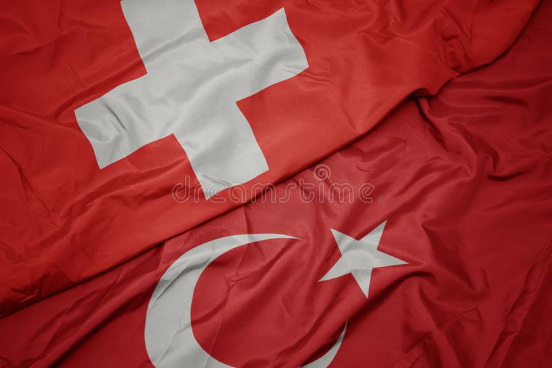 Waving colorful flag of turkey and national flag of switzerland. Macro royalty free stock images
