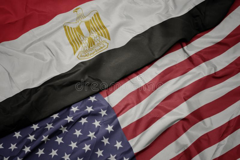 Waving colorful flag of united states of america and national flag of egypt. Macro royalty free stock image