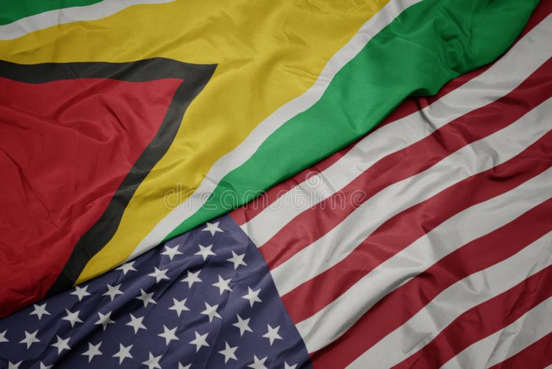 Waving colorful flag of united states of america and national flag of guyana. Macro stock photo