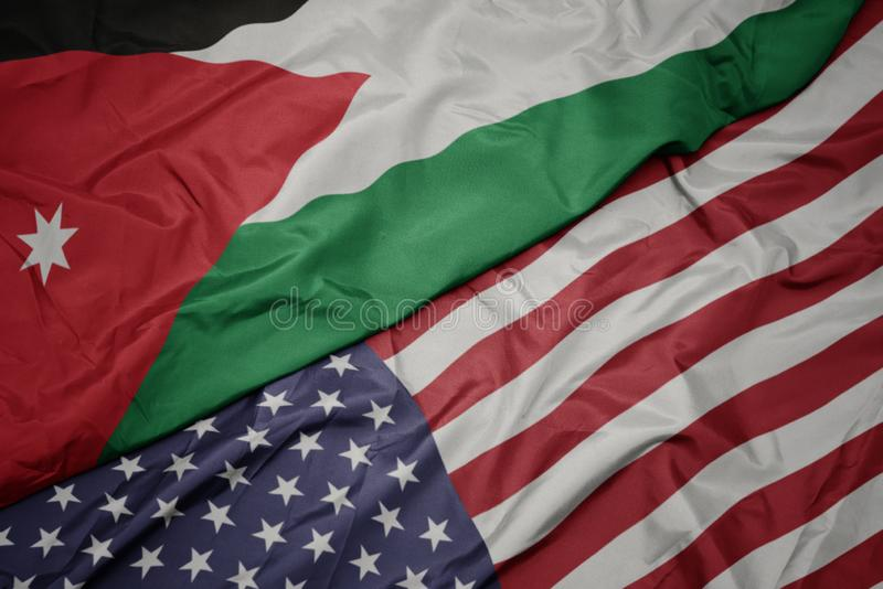 Waving colorful flag of united states of america and national flag of jordan. Macro stock photos