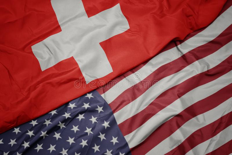 Waving colorful flag of united states of america and national flag of switzerland. macro. Waving colorful flag of united states of america and national flag of stock photos
