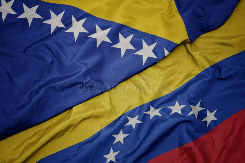Waving colorful flag of venezuela and national flag of bosnia and herzegovina. Macro stock photography