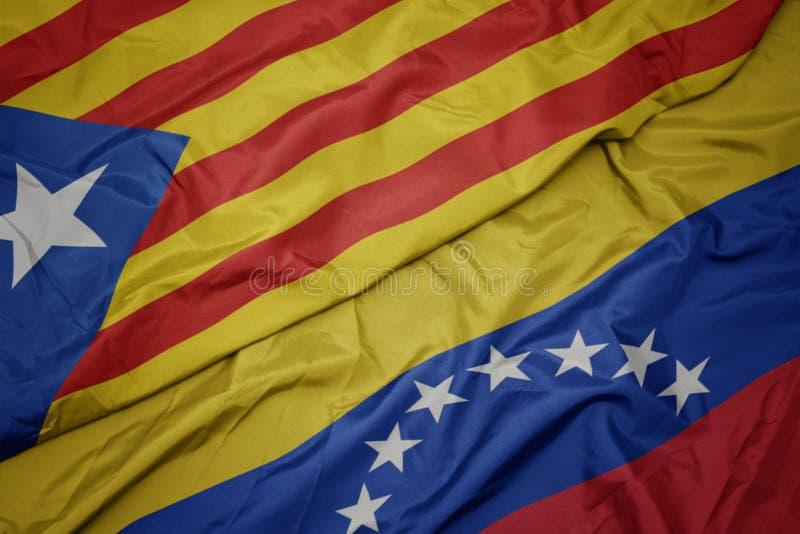 Waving colorful flag of venezuela and national flag of catalonia. Macro stock photography