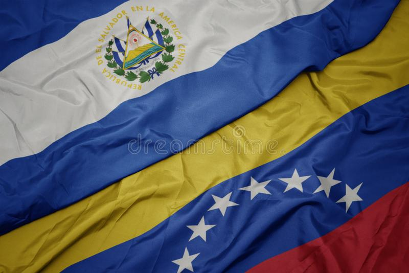 Waving colorful flag of venezuela and national flag of el salvador. Macro royalty free stock photography
