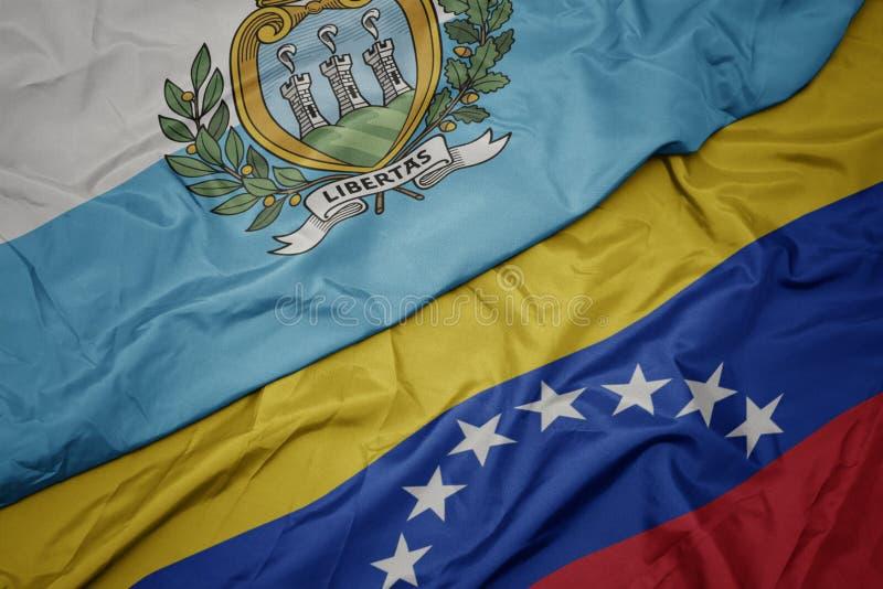 Waving colorful flag of venezuela and national flag of san marino. Macro royalty free stock image