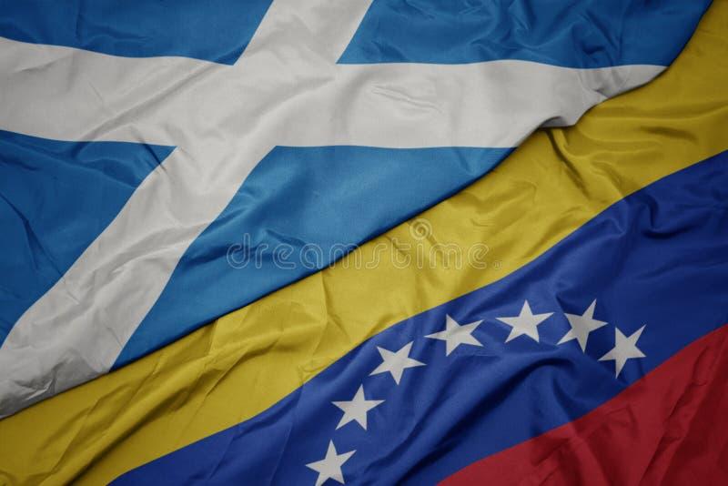 Waving colorful flag of venezuela and national flag of scotland. Macro royalty free stock photos