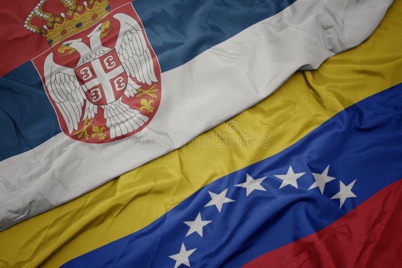 Waving colorful flag of venezuela and national flag of serbia. Macro royalty free stock photography
