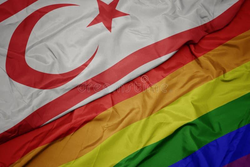Waving colorful gay rainbow flag and national flag of northern cyprus. Macro royalty free stock photos