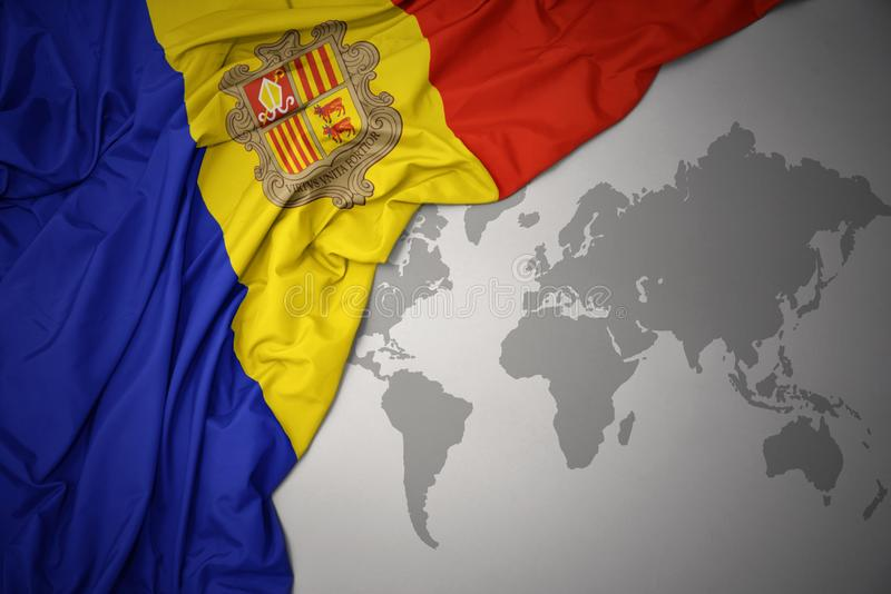Waving national flag of andorra. Waving colorful national flag of andorra on a gray world map background stock illustration