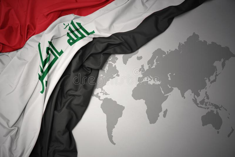 Waving colorful national flag of iraq. Waving colorful national flag of iraq on a gray world map background stock photography