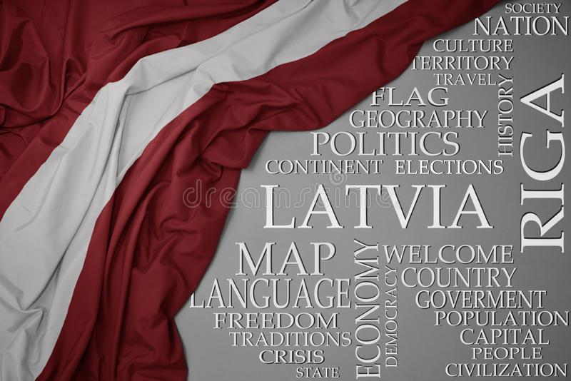 Waving colorful national flag of latvia on a gray background with important words about country. Concept stock photo