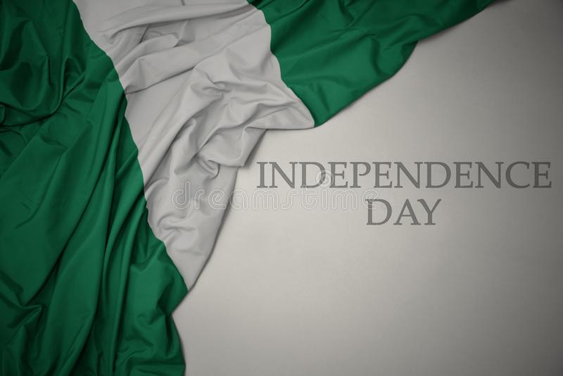 Waving colorful national flag of nigeria on a gray background with text independence day. Concept stock images