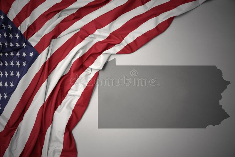 Waving national flag of united states of america on a gray pennsylvania state map background. Waving colorful national flag of united states of america on a royalty free stock photography