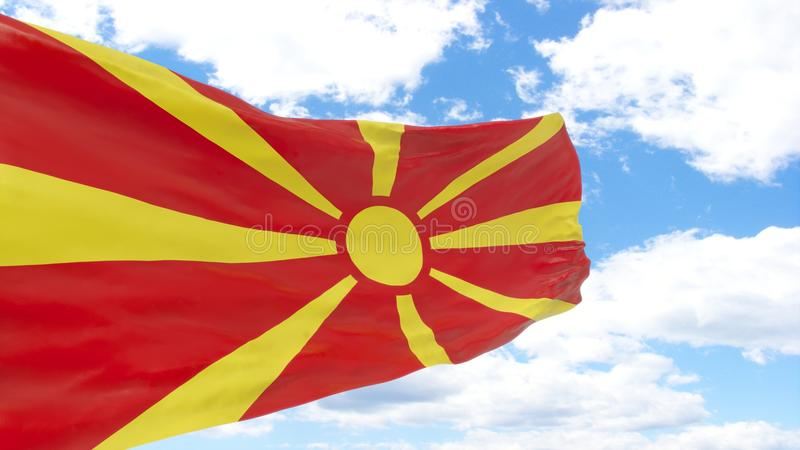 Waving flag of Macedonia on blue cloudy sky. royalty free stock images
