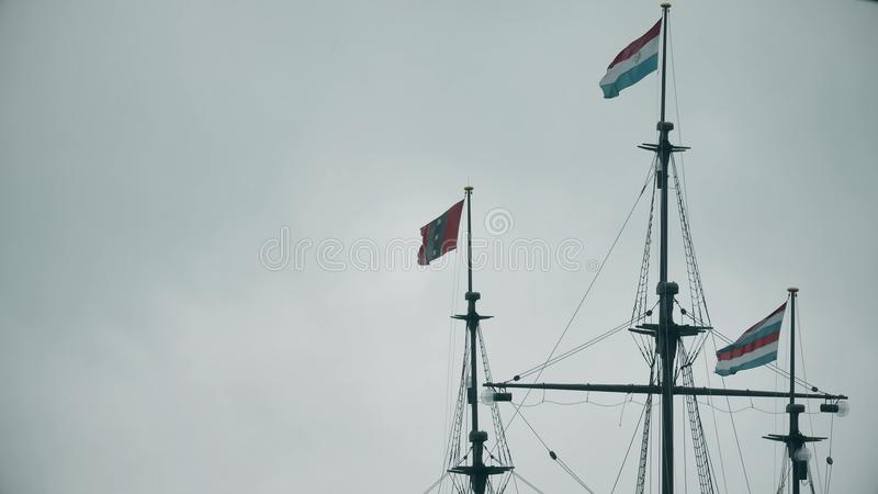 Waving flags of Netherlands and Amsterdam on the masts of an old ship memorial. Waving flags of Netherlands and Amsterdam on the masts of an old ship stock photos