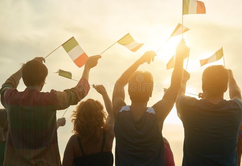Waving italian flags. Waving italian flags outdoors. Patriotic italilan family, rear view royalty free stock photos