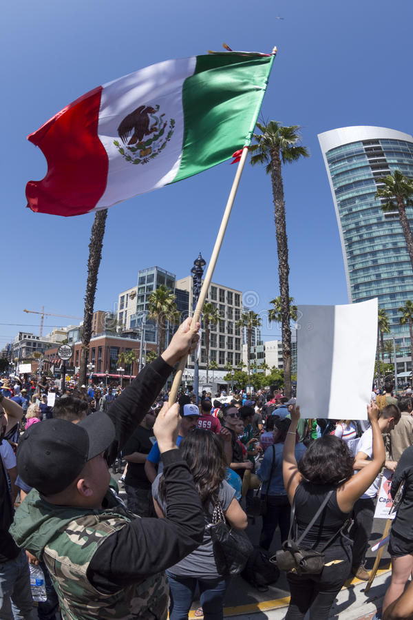 Waving Mexican flag at anti-Trump protest. SAN DIEGO, USA - MAY 27, 2016: A man waves the Mexican national flag high over head before a crowd protesting the royalty free stock images