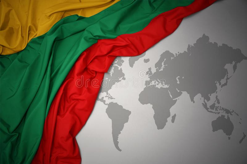 Waving national flag of lithuania. Waving colorful national flag of lithuania on a gray world map background vector illustration