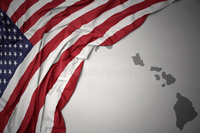 Waving national flag of united states of america on a gray hawaii state map background. Waving colorful national flag of united states of america on a gray royalty free stock photos