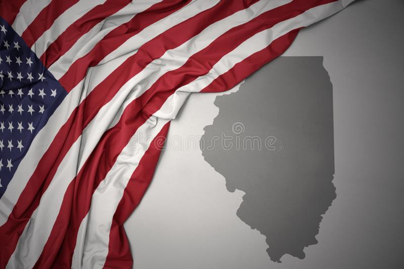 Waving national flag of united states of america on a gray illinois state map background. Waving colorful national flag of united states of america on a gray stock photo
