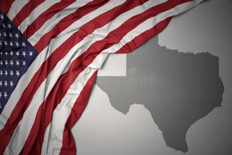 Waving national flag of united states of america on a gray texas state map background. Waving colorful national flag of united states of america on a gray texas stock photography