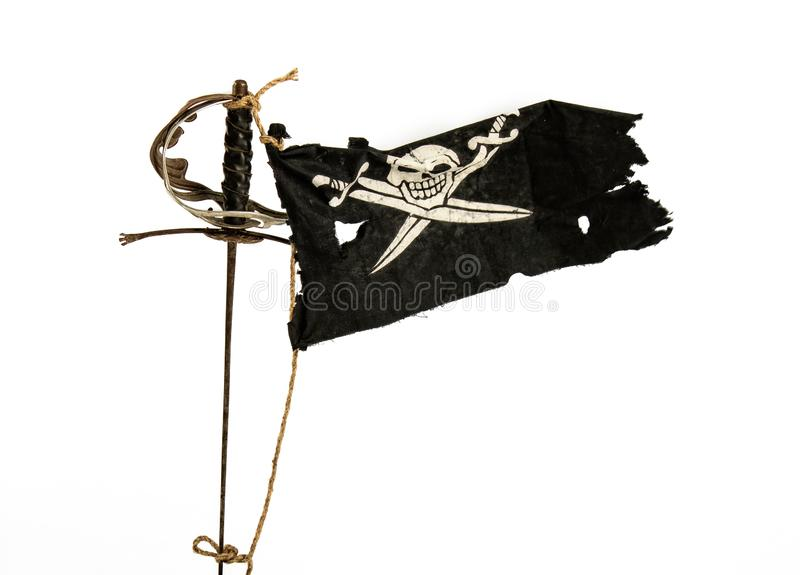 Waving pirate flag. Black pirate flag winding up in the wind tied with a rope to an old sword royalty free stock image